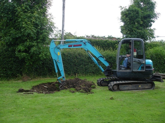 Man with a digger digging a whole